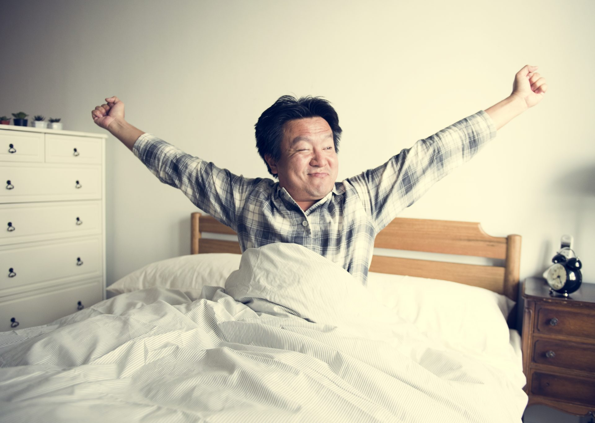 Middle-aged man stretches in bed after his insomnia has been helped by CBT-1 treatment at Synergy Counselling Kamloops